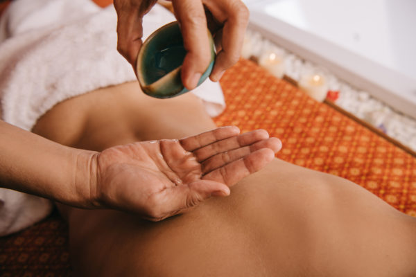 Massage therapist pouring oils for aromatherapy massage
